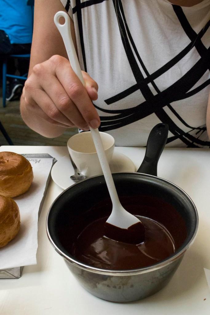 Chocolade smelten om te Bossche Bollen in te dopen tijdens de workshop Bossche Bollen maken in Bakkerij Royal in Den Bosch.