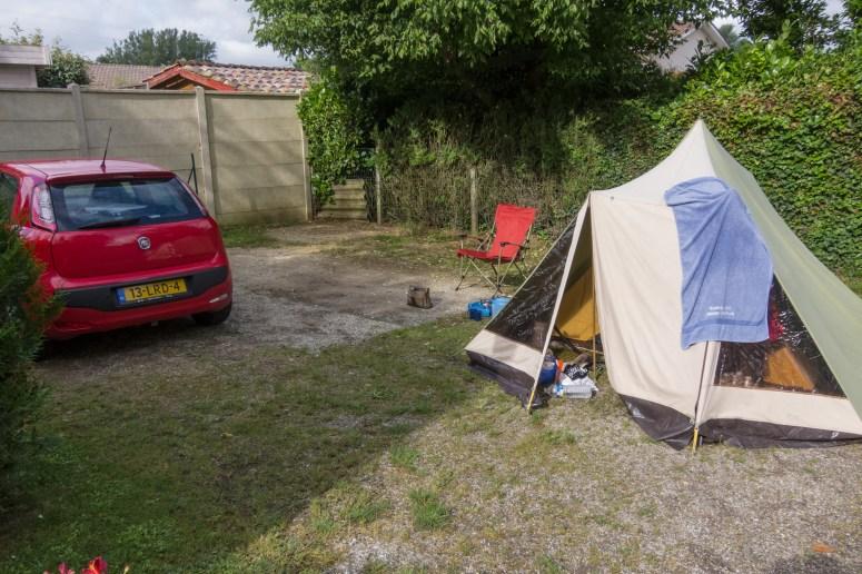 Kleine linnen tent met auto op een kale camping.