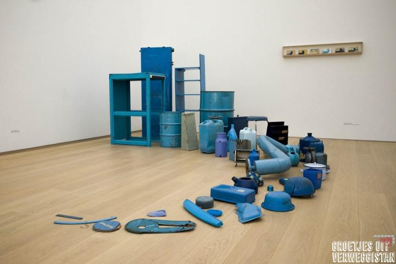 Een rij gebruiksvoorwerpen die blauw zijn gemaakt: kunstwerk van Tony Cragg,