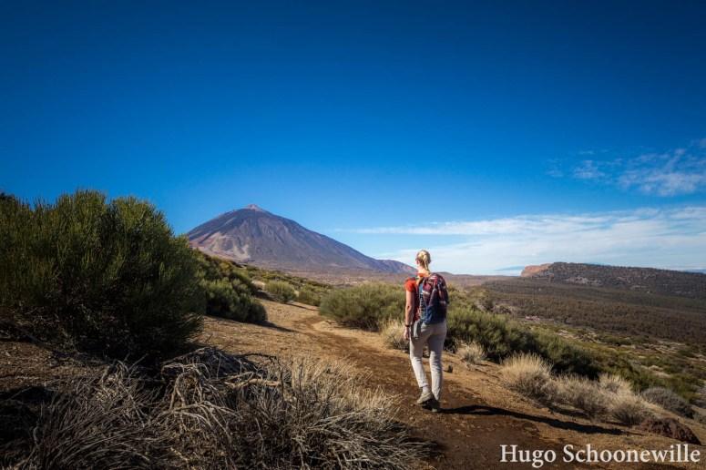 Meisje wandelt door National Park El Teide op Tenerife, met op achtergrond vulkaan El Teide.