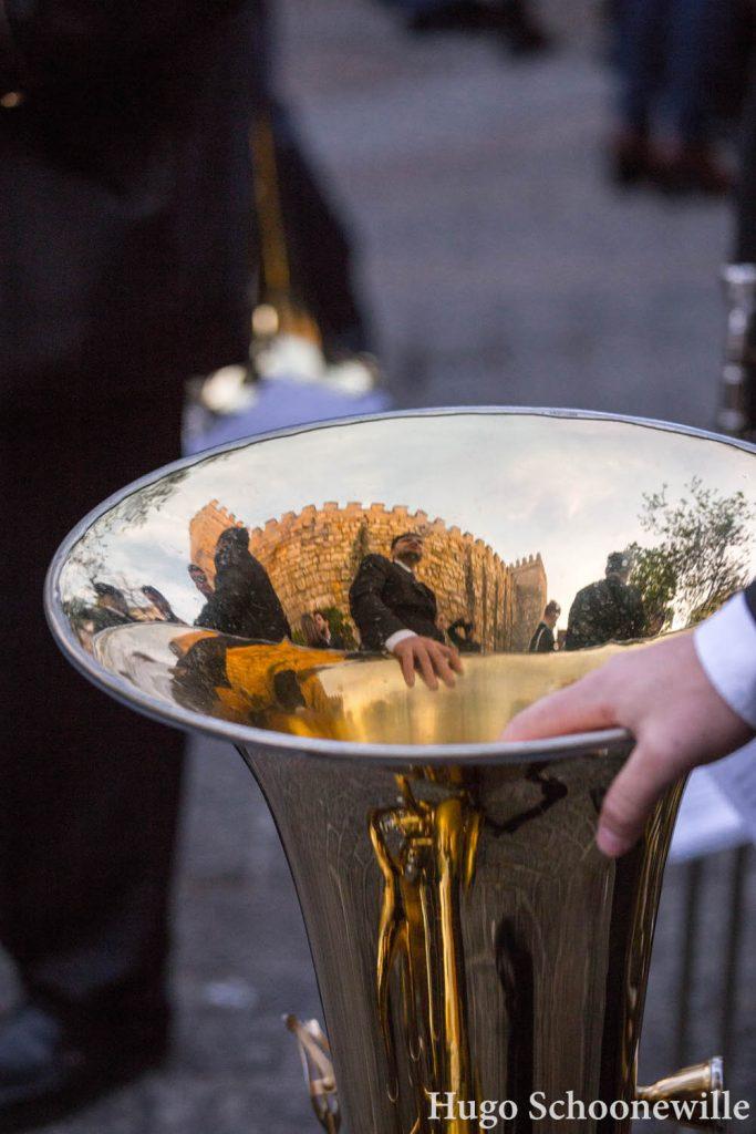 Muzikant houdt zijn tuba vast op de grond en in de hoorn weerspiegelt het Alcazar van Sevilla