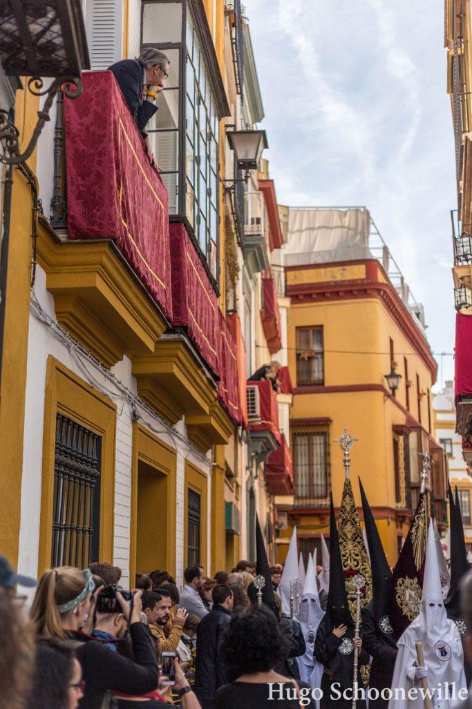 Paso in de smalle straatjes van Sevilla met mensen op de balkons die kijken