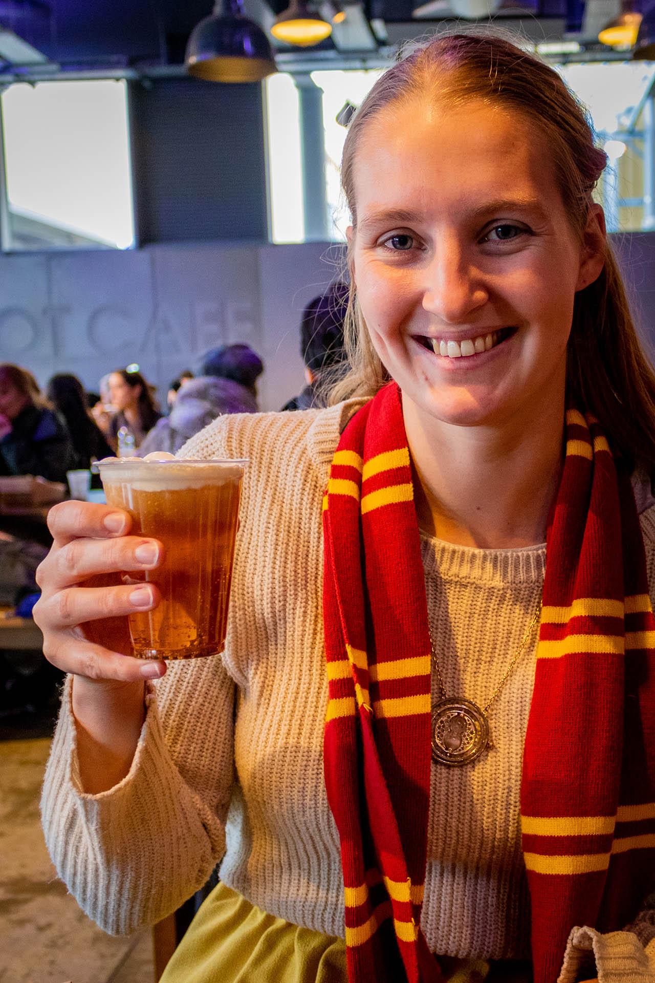 Meisje met glas boterbier of butterbeer in de Warner Bros. Studio Tour in Londen met Gryffindor sjaal