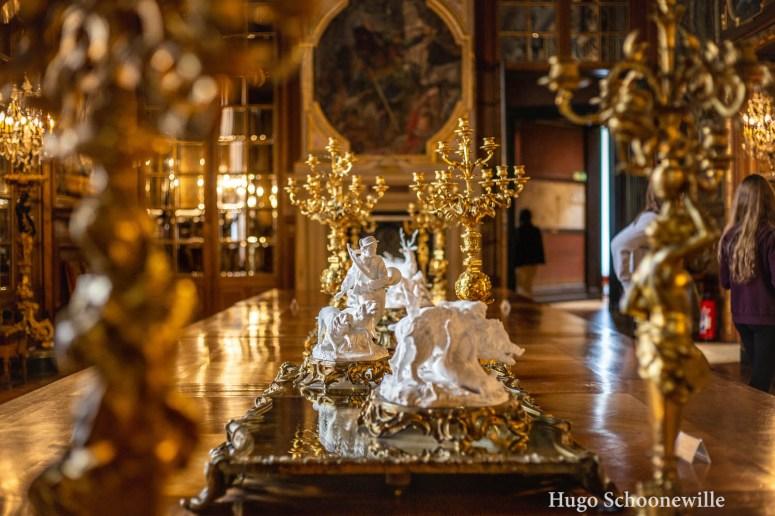 Beeldjes en gouden kandelaren op een lange tafel in een zaal in het kasteel van Chantilly.