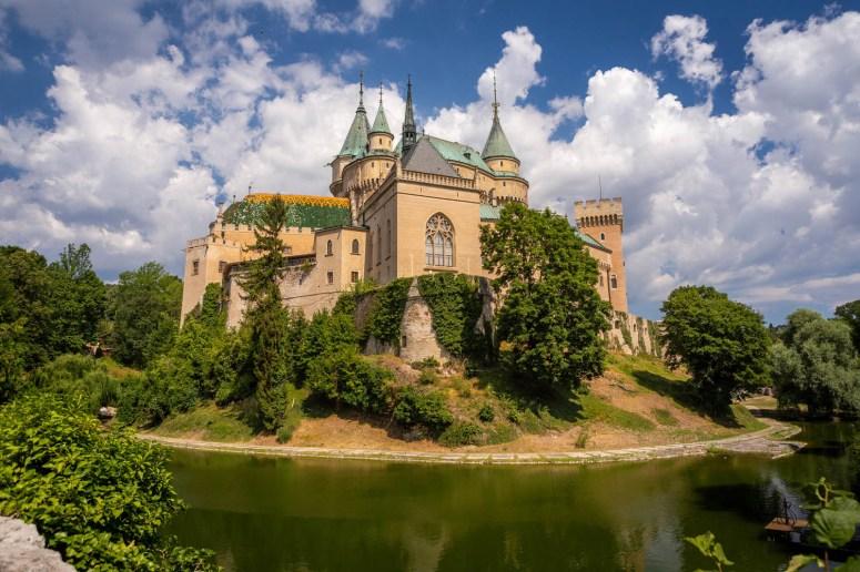 Het sprookjesachtige kasteel Bojnice in Slowakije met slotgracht, torentjes en blauwe lucht