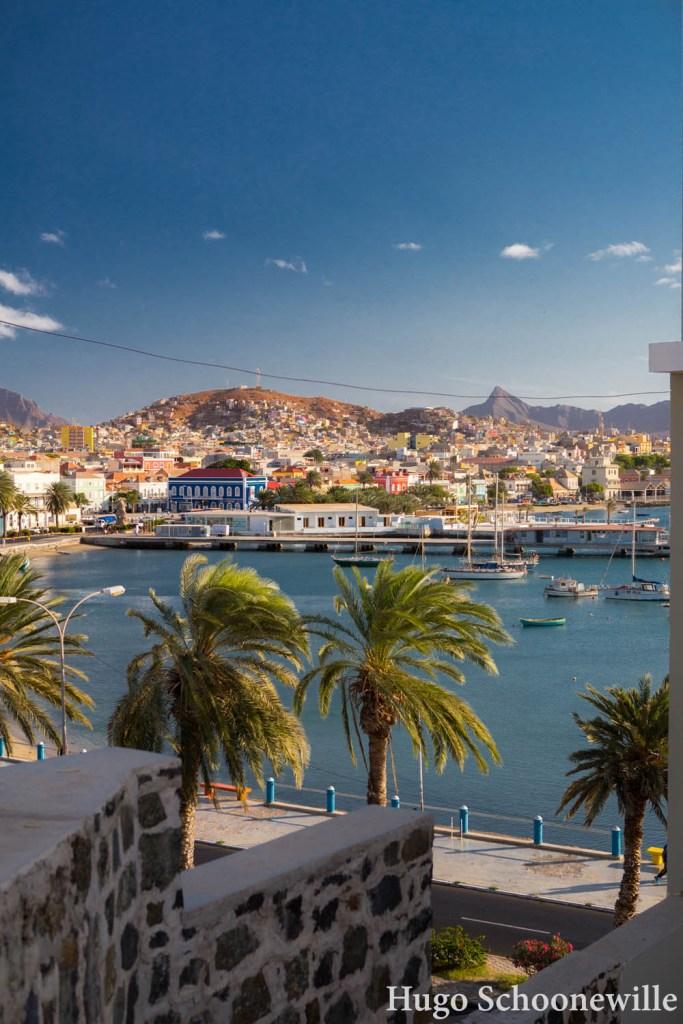 Uitzicht over de haven van Mindelo, met palmbomen, boten en de stad op de achtergrond.