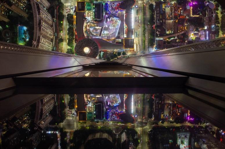 Neerkijkend op Shenzhen vanaf een hoog gebouw met reflectie in de ramen.