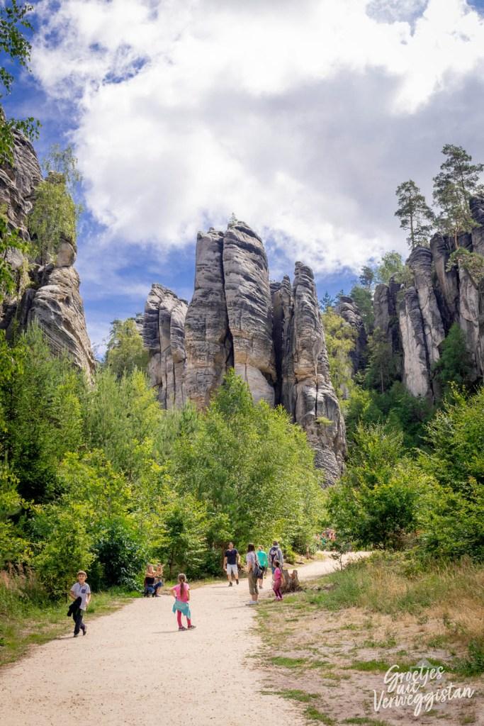 Eerste blik op de rotsen van Prachov vanaf beneden, ze torenen boven het pad uit.