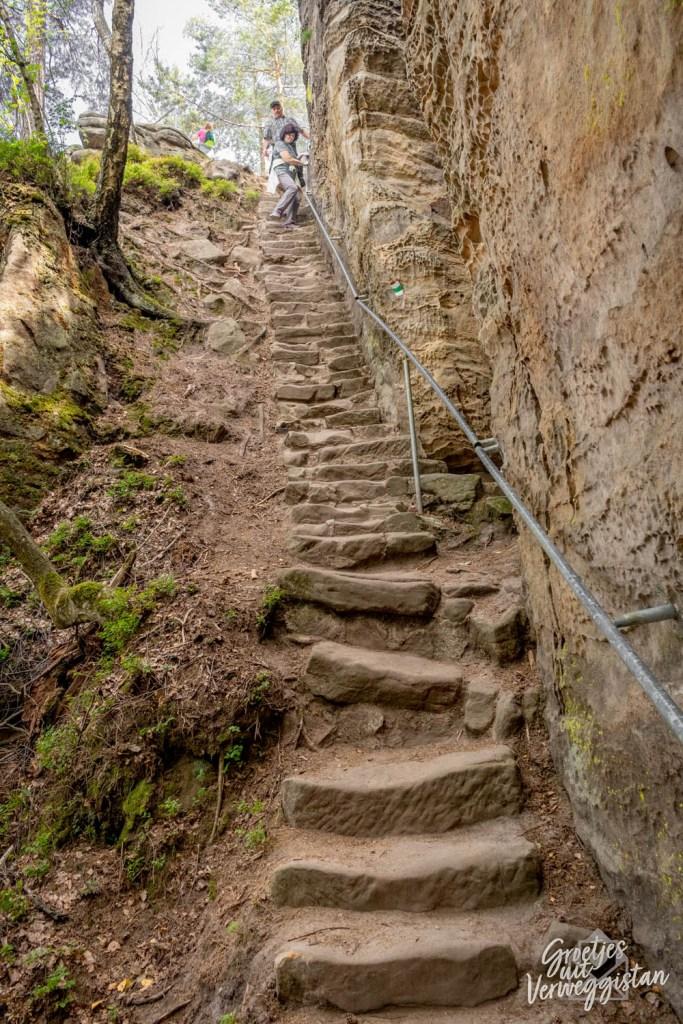 Steile trap uitgehakt in de rotsen met een leuning.