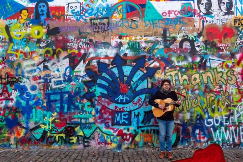 Beschildere John Lennon Wall in Praag met ervoor een muzikant met een gitaar