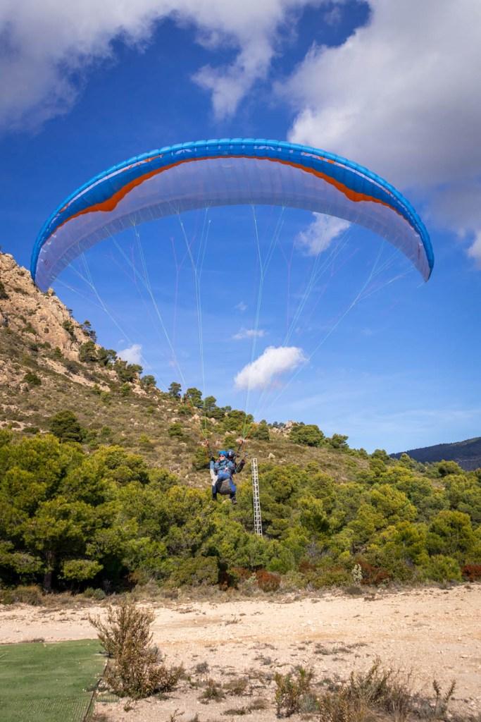 Kelly en piloot Juan aan de parachute komen steeds dichter bij de grond.
