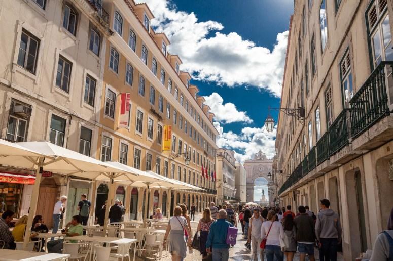 Een van de brede straten in de wijk Baixa, met links en rechts 5-verdiepingen hoge gebouwen en in de verte de toegangspoort Arco da Rua Augusta