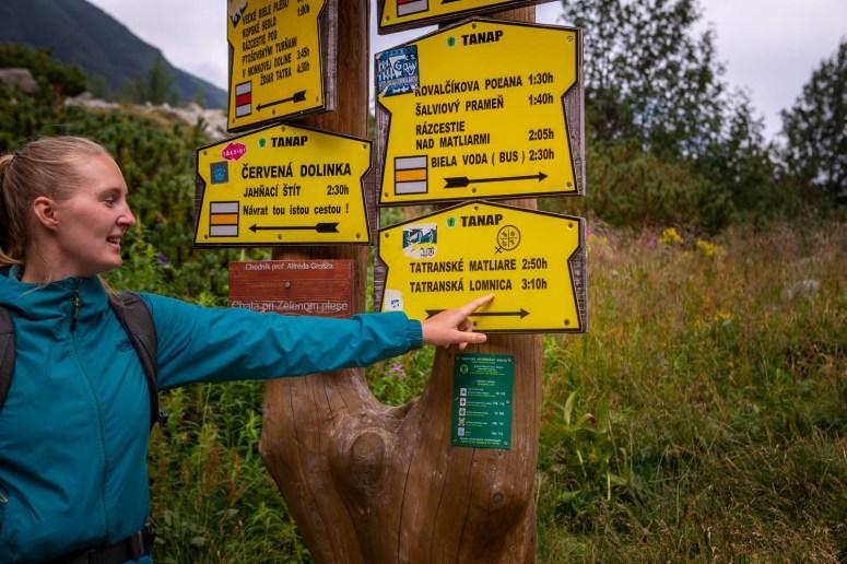 Manouk wijst 'Tatranská Lomnica' aan op een geel bordje met routeaanwijzingen in Slowakije.