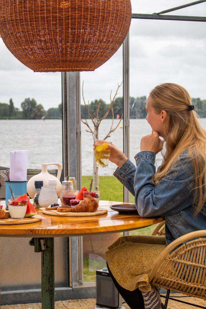 Manouk met een glas thee tijdens het ontbijt in een kas bij Brasserie Buitenhuis
