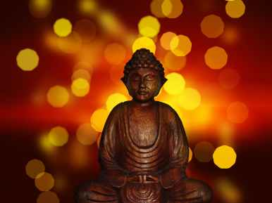 "Alt=""Bronze buddha statue in front of gold and red lights"""