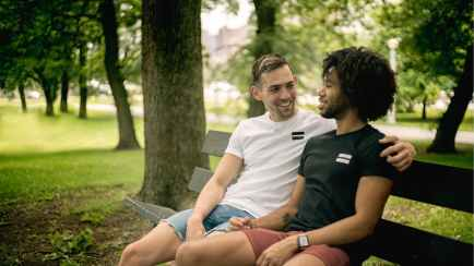 "Alt=""Interracial gay male couple sitting on a park bench"""