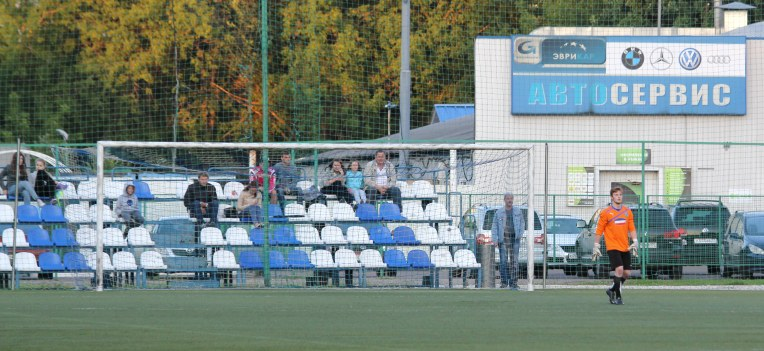 A handful of fans and a car repair shop - a typical scene from Russian amateur football. Burevestnik vs Troitsk, Moscow, summer 2015.