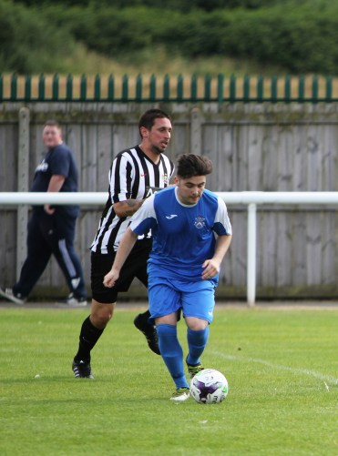 Kieran Turner (blue) gets away from James Harmison of Ashington on his way to scoring Nelson's opening goal.