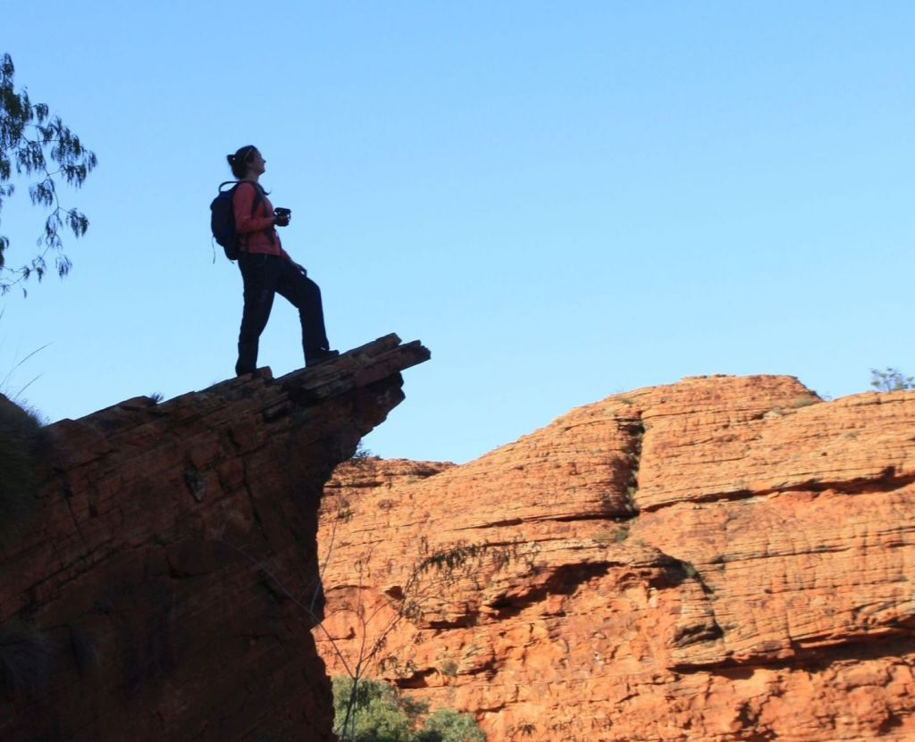 Woman in hiking clothes standing confidently close to the edge of a rocky outcrop, looking over a central Australian valley with cliffs