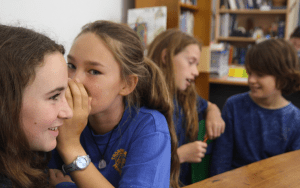 Classroom with 4 12-year-old students. A girl is whispering into the ear of another girl while two boys in the background are chatting with each other