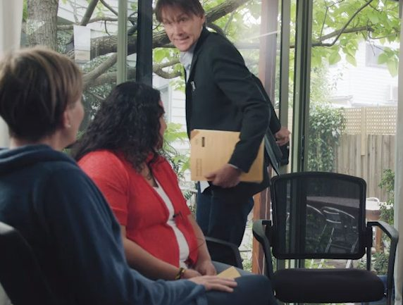 Informal office setting with windows, two women sitting in chairs looking up at a man entering the room with a stressed look on his face