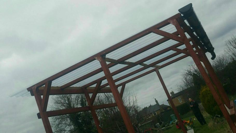 frame of our open shed pergola type thing with plastic corrugated roofing and guttering to catch water