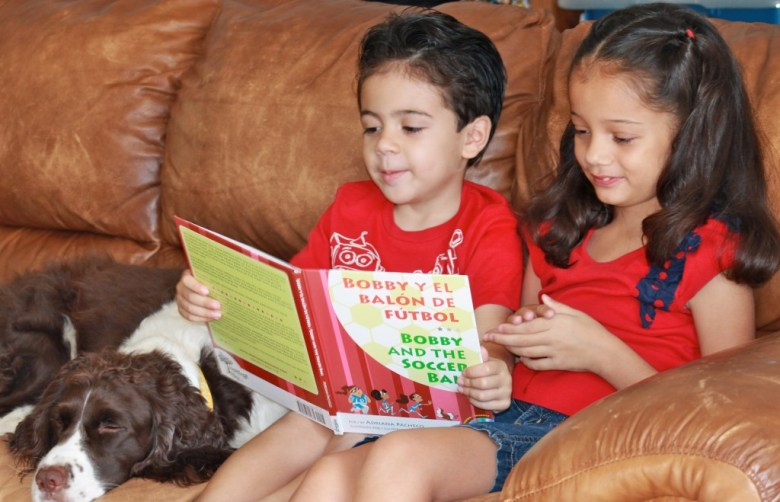 boy and girl reading book in spanish with dog