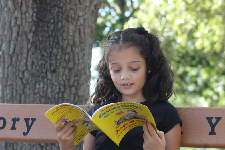 girl reading bilingual Curious George book