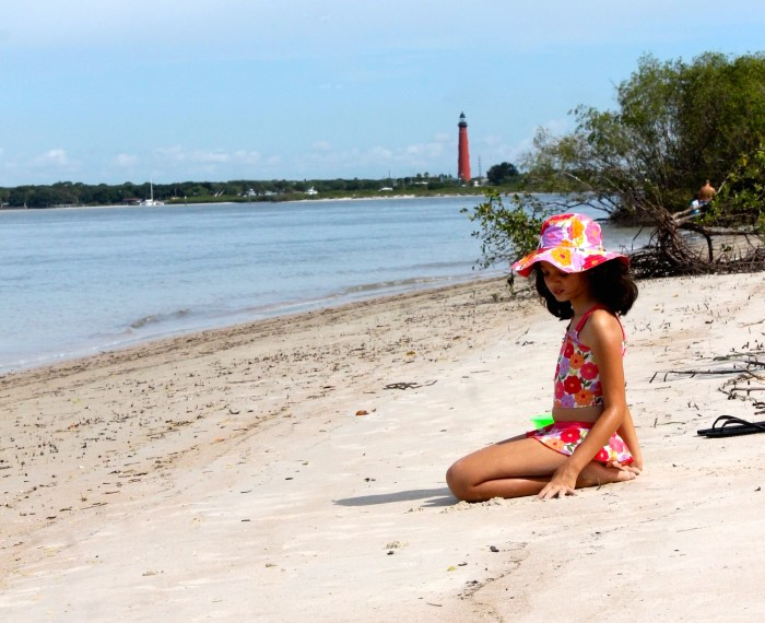girl at the beach with lighthouse in the background at dunes park in New Smyrna beach