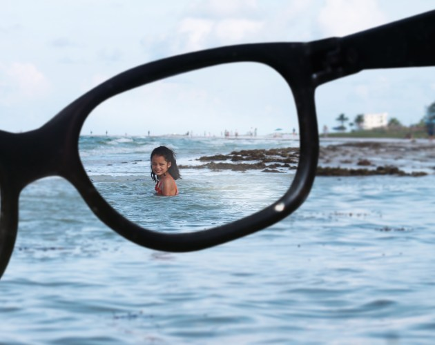 beach and girl seen through eyeglasses