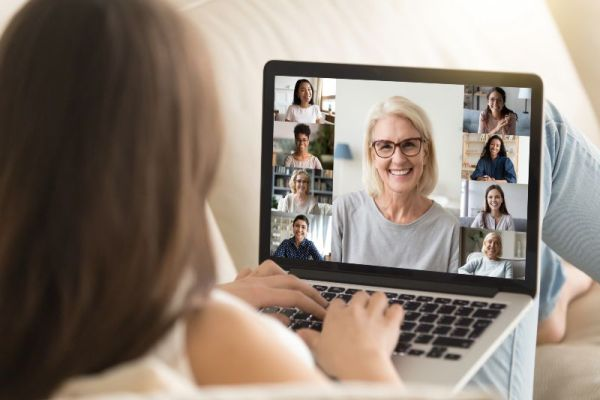 older woman in glasses smiling on laptop screen during virtual event | Your Complete Guide to Hosting Successful Virtual Events on Alignable https://growyourbusiness.alignable.com/alignable-101/how-to-host-virtual-events-on-alignable