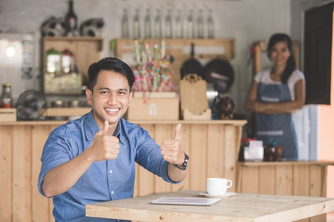 man sitting in cafe with two thumbs up