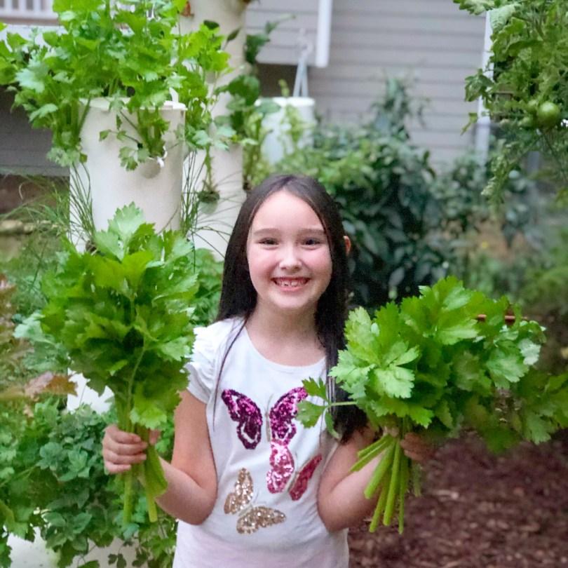 Happy little girl double-fisting celery harvest