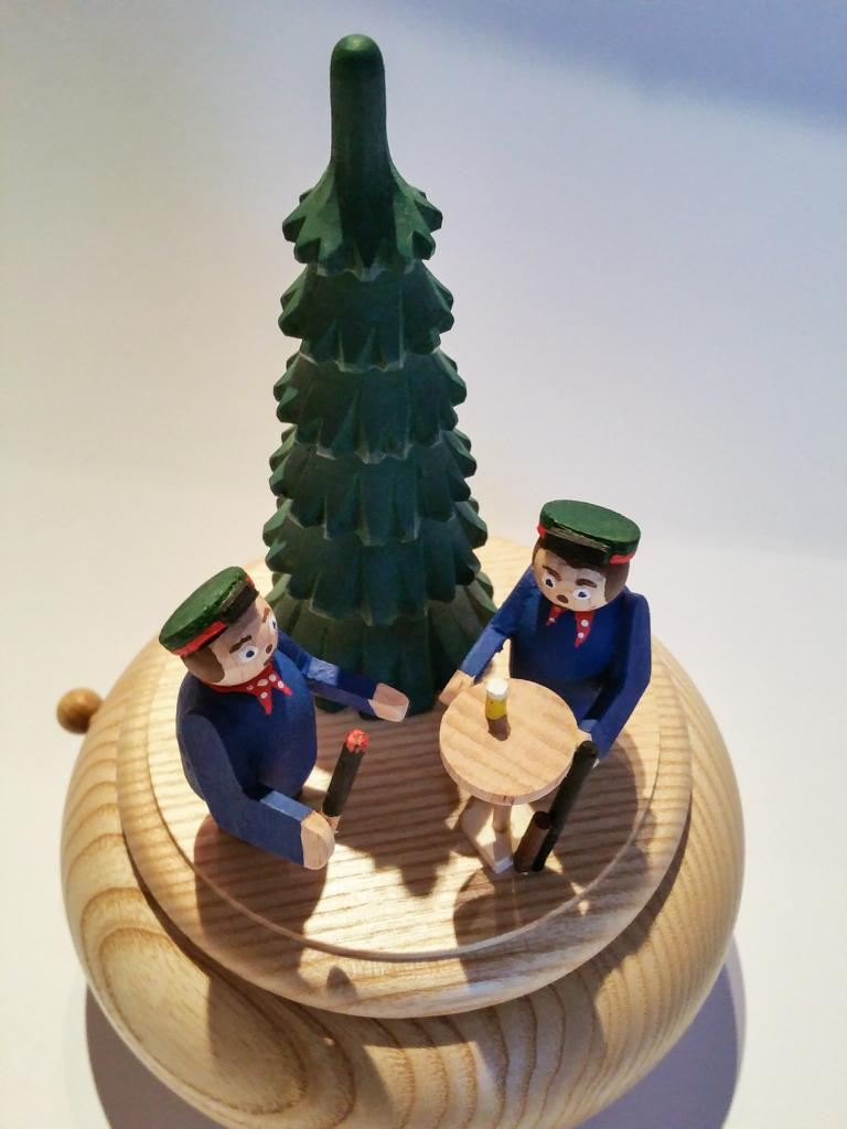 Spieldose, gestaltet von Detlev Gröschl, mit Meinerzhagener Schützen samt Tannenbaum, Fackel und einem Stehtisch, darauf (ebenfalls aus Holz) ein Glas Bier mit Schaum. © 2016 Foto: Stefanie Schildchen