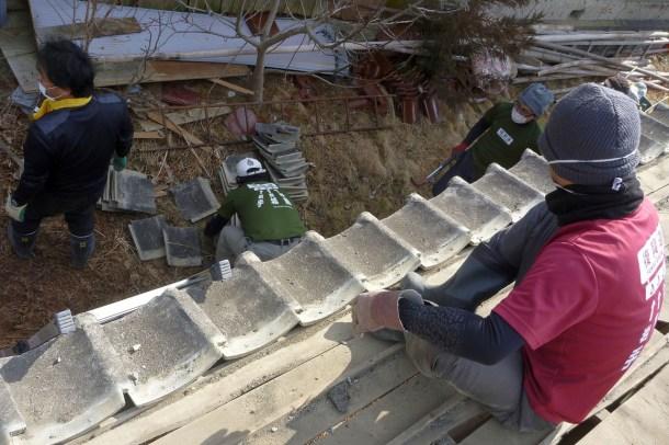 """Auch kein Einzelfall: In Fukushima räumen sogenannte Freiwillige nach der Reaktorkatastrophe auf, hier wird ein Dach in Minamisoma in der Nähe des Kraftwerks abgedeckt. Berge kontaminierten Mülls in der verlorenen Heimat sind das emotionale Thema der Katastrophe von 2011, der Rückbau der havarierten Reaktoren das ökonomische Problem: 150 Milliarden werden die Entsorgungsarbeiten allein am Reaktor kosten, schätzt die FAZ.  Die WDR Wirtschaftsredaktion hat die Kosten aller AKW-Unfälle, gescheiterter Endlagerprojekte, Kosten ungenutzter Anlagen und Schäden durch Uran-Abbaubetriebe addiert und präsentierte die Zahl von 1,018 Billionen Dollar für den volkswirtschaftlichen Schaden der zivilen Nutzung der Kernenergie bis heute in dem Beitrag """"Das Billionen-Dollar-Desaster"""". (Foto: Hajime Nakano / Flickr.com / CC BY 2.0)"""