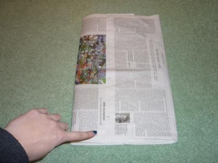 Für die gerade Tüte wird die Doppelseite einer Zeitung oder Zeitschrift von beiden Seiten in die Mitte gefaltet. Die Kanten müssen sich dabei in der Mitte überschneiden.