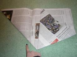Das Papier wird zu einem Dreieck gefaltet. Dann wird eine der spitzen Ecken auf die gegenüberliegende Seite geklappt. Der Winkel bestimmt die Größe der Tüte. Die untere Seite (Fingerzeig!) wird später der Boden des Beutels sein.