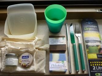 Nachhaltiges Travelset (von links oben im Uhrzeigersinn): 1. Box, 2. Plastikbecher, 3. DrySack, 4. Besteck, 5. Edelstahlstrohhalm, 6. Haarseife, 7. Wäscheseife, 8. Lippenpflege, 9. Creme im Glas, 10. Beutel für Obst, 11. Jutebeutel
