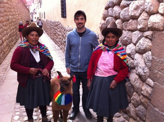 Posing with a baby alpaca and two local women