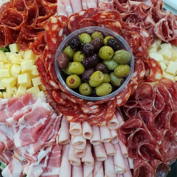 A generous platter with rolled pieces of ham, salami, cubes of cheese and a bowl of mixed olives in the centre.