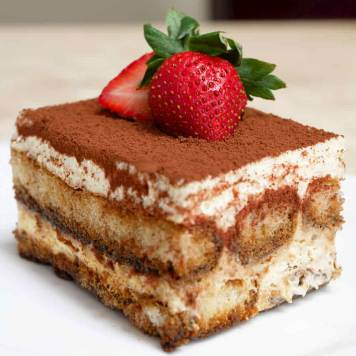 A square slice of sponge based cake dusted with chocolate with two strawberries on top.