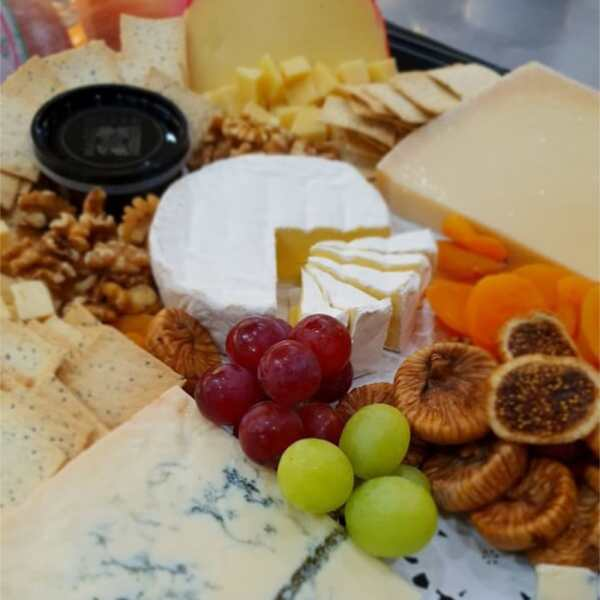 A plate of mixed cheeses with dried figs and grapes.