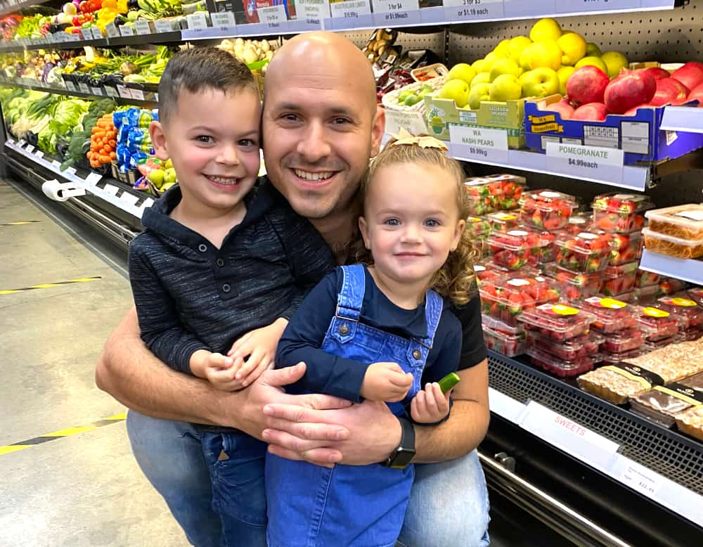 Giusep hugging his two little kids in front of the produce chiller.