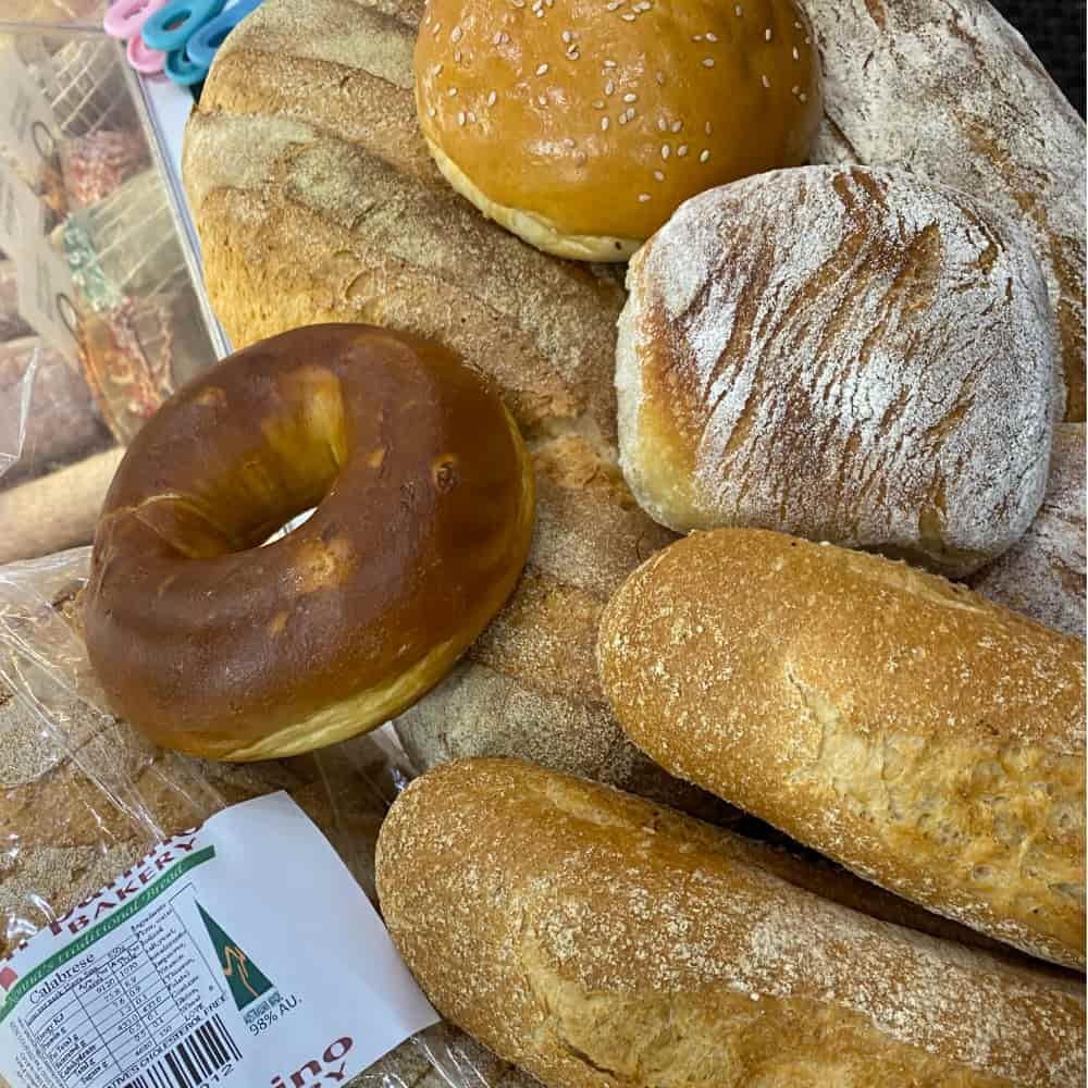 A selection of bread rolls and a donut piled together.