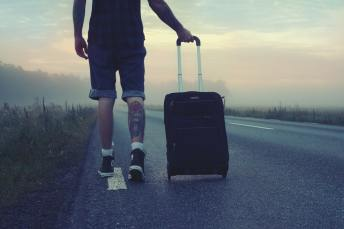 A man walking on the side of a road with a suitcase