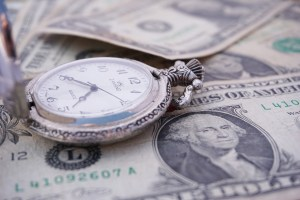 A pocket watch lying on dollar bills