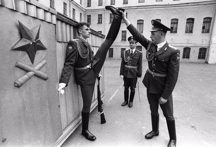 Un militar Ruso sujeta la pierna de otro militar por encima de su cabeza haciendo que sus piernas formen un ángulo de 180º