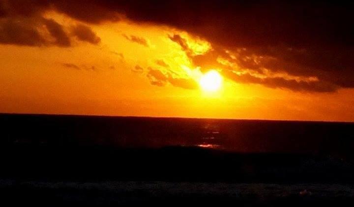 un atardecer en el mar con un cielo ligeramente nublado