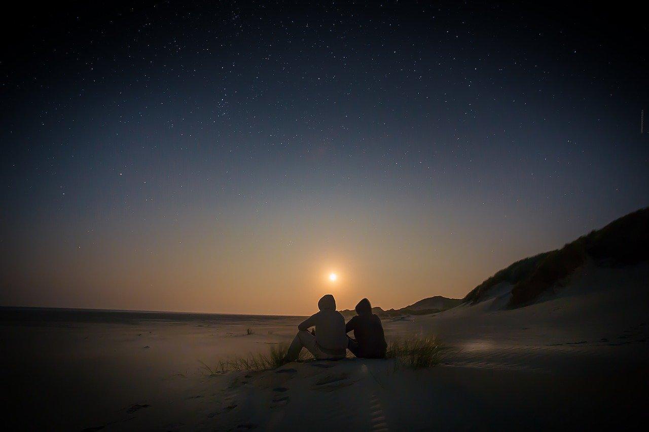 Una pareja al atardece en una playa a contraluz