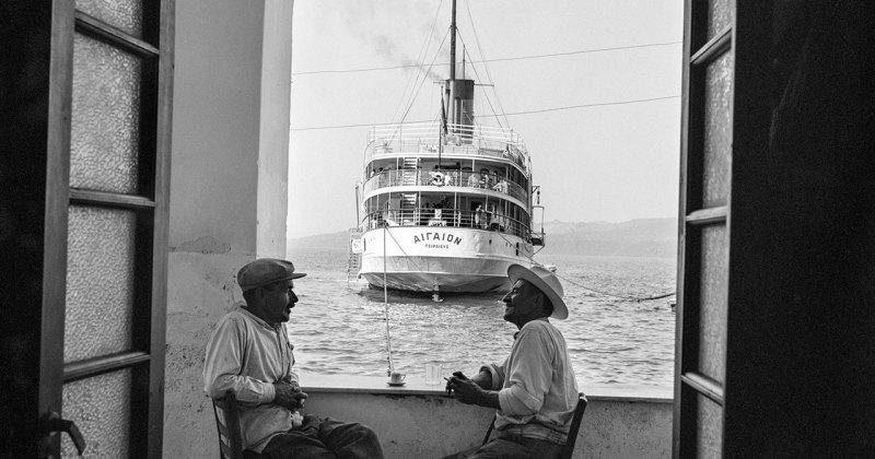 Un paer de hombre charlando con un barco que se aleja (fotografía: Santorini 1954 @Robert MacCabe)